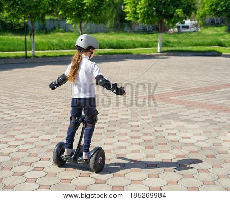 Small girl learns to ride electric mini hoverboard in the city