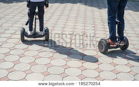 Young father and daughter riding electric mini hoverboard in park. Family concept. Close up leg view