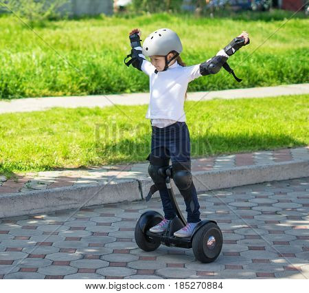Happy small girllearned to ride electric mini hoverboard or a gyroboard in the city. She is glad and shows happy gesture