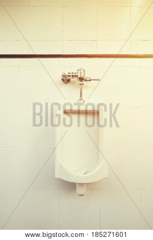 White urinal for men on tile wall in toilet.