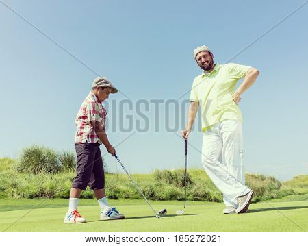 Father teaching son playing golf at club