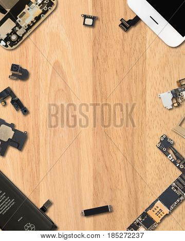 Flat Lay (Top view) of smartphone components on wooden background with copy space in 4:5 aspect ratio