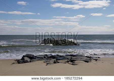 Exterior daytime stock photo of rocks off the shoreline of beach in Spring Lake, New Jersey on sunny morning.