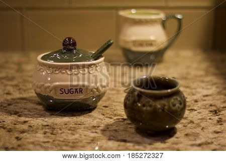 Shallow depth of field Irish sugar container on brown and white granite kitchen countertop with Irish creamer container in the background backed by clear tile backsplash