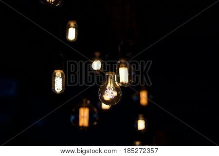 Shallow depth of field interior stock of hanging vintage electric lights hanging in brewpub in East Auroroa, New York in Erie County