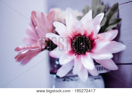 Shallow depth of field interior stock photo of pink and white fabric flower in ball jar attached to wooden pallet frame