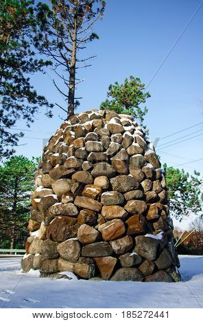 Exterior daytime winter picture of stone obelisk structure in snowy chestnut ridge park in Orchard Park, New York with blue sky and evergreen trees in the background