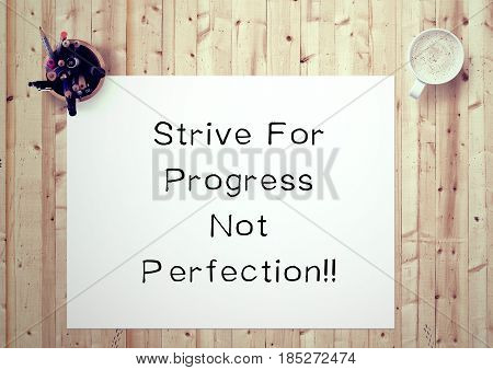 Inspiring motivation quote handwritten on a notepad strive for progress not perfection. White pad paper image.