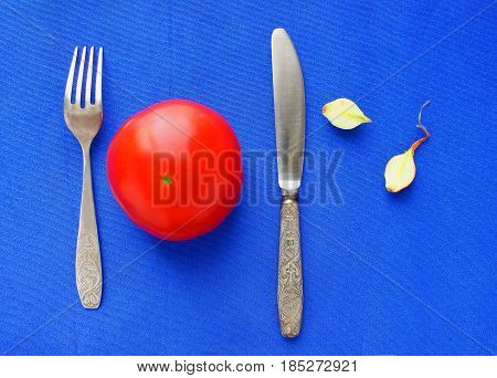 Still life one ripe red tomato, Blue background, fork, knife, onion