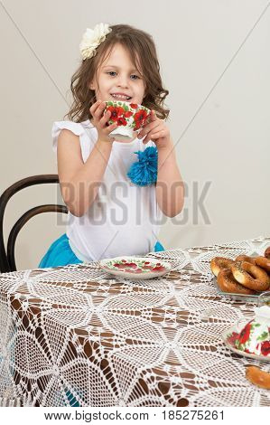 Beautiful little girl drinking tea from a mug sitting at grandma's old table , covered with a lace tablecloth.
