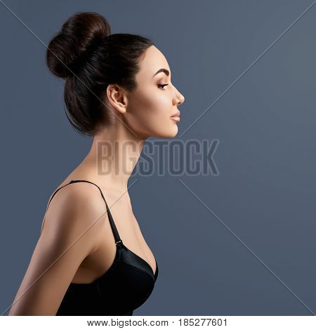 Portrait of beautiful woman, profile. silhouette of attractive girl in studio over gray background with copy space.