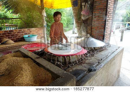 Can Tho city, Viet Nam - January 12, 2017: Undefined cooker make rice pancakes drying on the sun in the rice noodles factory, Can Tho (Mekong Delta), South Vietnam