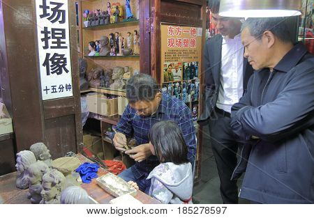 HANGZHOU CHINA - NOVEMBER 5, 2016: Unidentified people watch handicraft demonstration on Qing He Fang street. is a protected area of the historical buildings from the Ming and Qing dynasty.