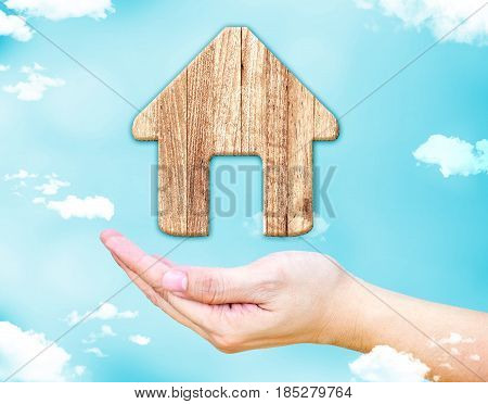 Open female hand with Home wood icon with blue sky and cloud Real estate concept.3d rendering icon