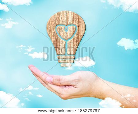 Open female hand with Heart in lightbulb wood icon with blue sky and cloud Creative idea concept.3d rendering icon
