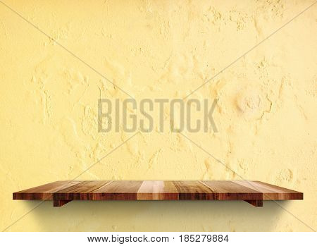 Empty Wooden Shelfs On Pastel Grunge Yellow Concrete Wall, Mock Up Template For Display Of Product