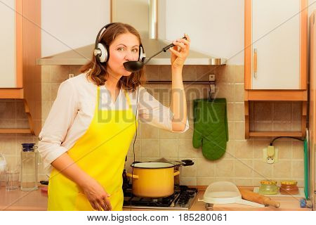 Cooking and preparing food concept. Relaxed beauty woman housewife chef with earphones listening music in house kitchen making dinner meal.