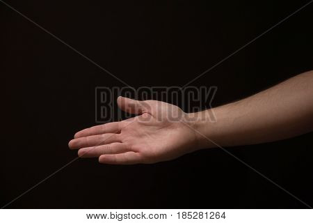 Open Male Hand Coming Out Of The Right Side Of The Frame, On A Black Background