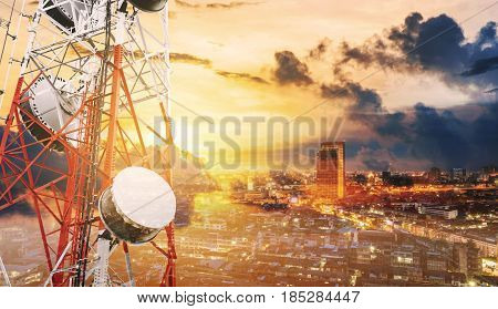 Double exposure telecommunication towers with TV antennas and satellite dish in sunset, with city background