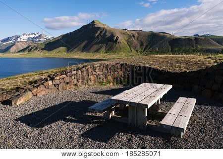 Survey site overlooking the mountains and the lake in Iceland. Place to relax with wooden benches and a table. Summer sunny day