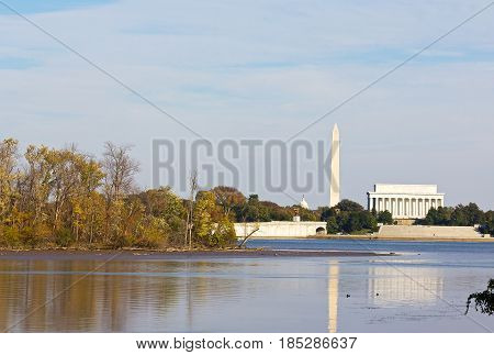 Washington DC landmarks in autumn. US capital monuments with reflection in Potomac River in fall.