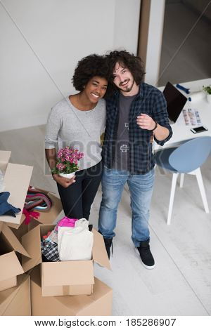 Happy young multiethnic couple unpacking or packing boxes and moving into a new home