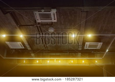 spotlights on a rail and ceiling mounted air conditioner in exhibition room ceiling system