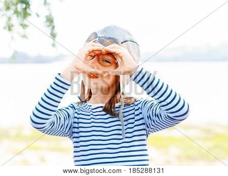 Young happy little girl with sailor shirt and aviator hat play with hands in front of Danube river.