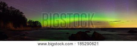 Starry sky and aurora borealis over stony sea shore panoramic view