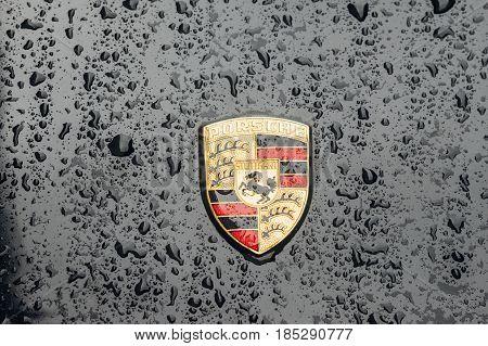 Tallinn Estonia - April 30 2017: Closeup on logo of Porsche AG with rain drops. Porsche is a german automobile manufacturer specializing in high-performance sports cars.