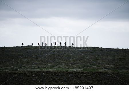 Hill near the glacial lake Fjallsarlon. Vatnajokull National Park, Iceland. 10 June 2016: Group of tourists with backpacks are walking along the crest of the ridge.