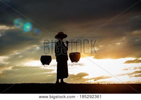 Old farmer with a bamboo basket on a field at sunset.