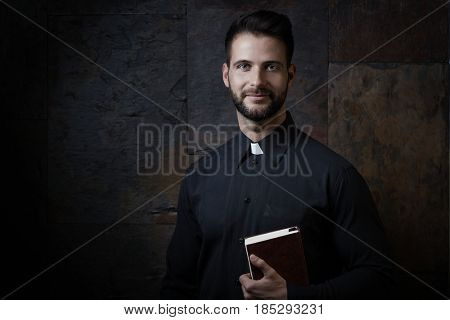 Portrait of handsome young priest with prayer book against dark background.