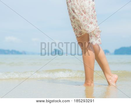 Beach travel - woman walking on sand beach. Closeup detail of female feet .Step up concept.