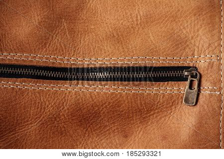 surface of old brown leather and zipper.