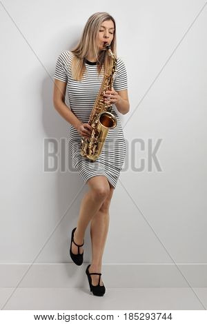 Full length portrait of a young woman in a dress playing a saxophone and leaning against a wall