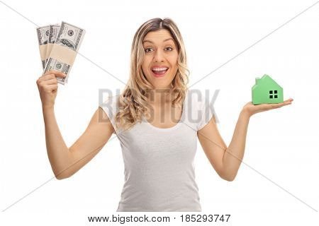 Joyful woman holding bundles of money and a model house isolated on white background