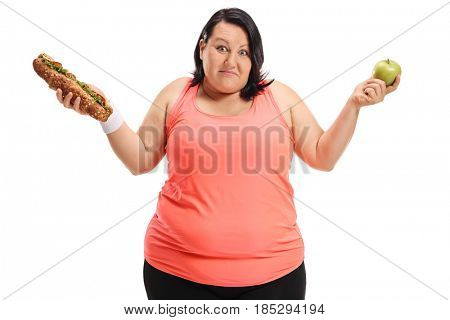Indecisive overweight woman holding a sandwich and an apple isolated on white background