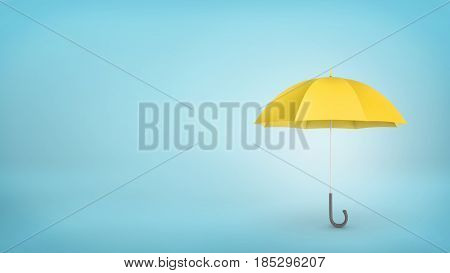 An open classic yellow umbrella with a handle vertically placed on blue background. Rainy weather. Protection and safety. Umbrellas and parasols.