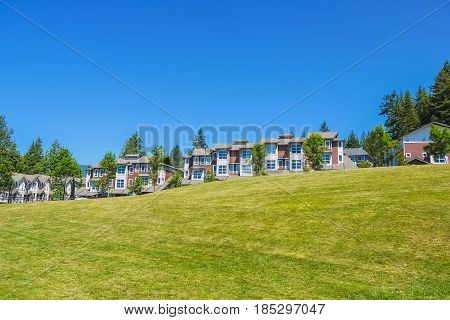 Row of new townhouses on top of the hill on sunny day in British Columbia