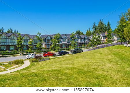 Row of new townhouses with recreation area across the road and parked car on the road
