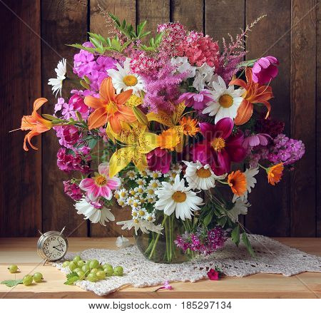country still life with a bouquet of garden flowers in a glass jug and an alarm clock in rustic style