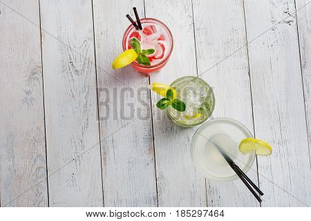 Colorful cocktails set. Mojito , Margarita, red alcohol cocktail on wooden table close up .