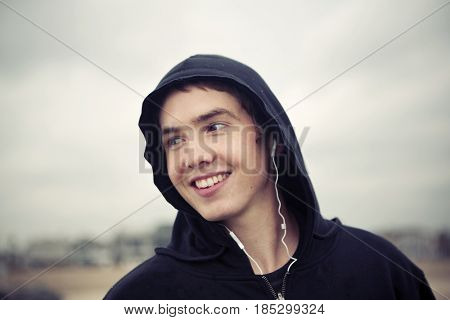 Caucasian man wearing hoody listening to earbuds