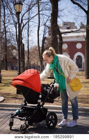 Young happy woman walking with stroller in the city. Mother with baby child in a pram. Lifestyle concept