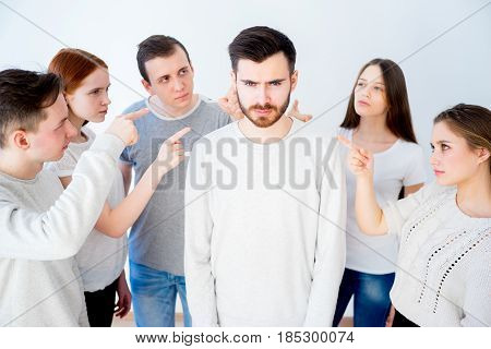 Concept of accusation - group of people pointing at a man