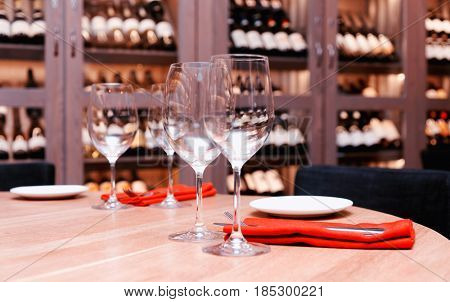 Restaurant table with wine cellar in blurred background, toned image