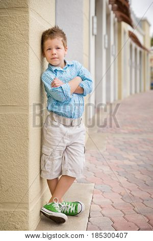 Kids fashion concept. casual child stands with his back against street wall.Outdoor portrait of a cute little blond boy wearing shorts and shirt standing next to stone wall