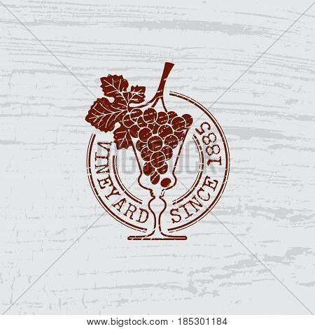 Wine glass and bunch of grapes with scratches on wooden background. Template for logo stamp label emblem for wine collection wine bar menu restaurant wine list vineyard. Vector illustration.