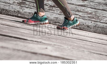 female legs in tights and sports shoes on wooden background , concept sports